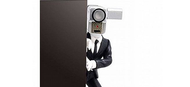 カメラ男が机の上から覗き見。机の上の「NO MORE 映画泥棒」が8月下旬発売